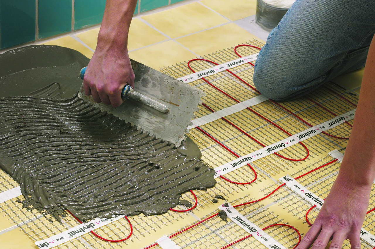 Слой плиточного клея укладывается прямо на нагревательные маты