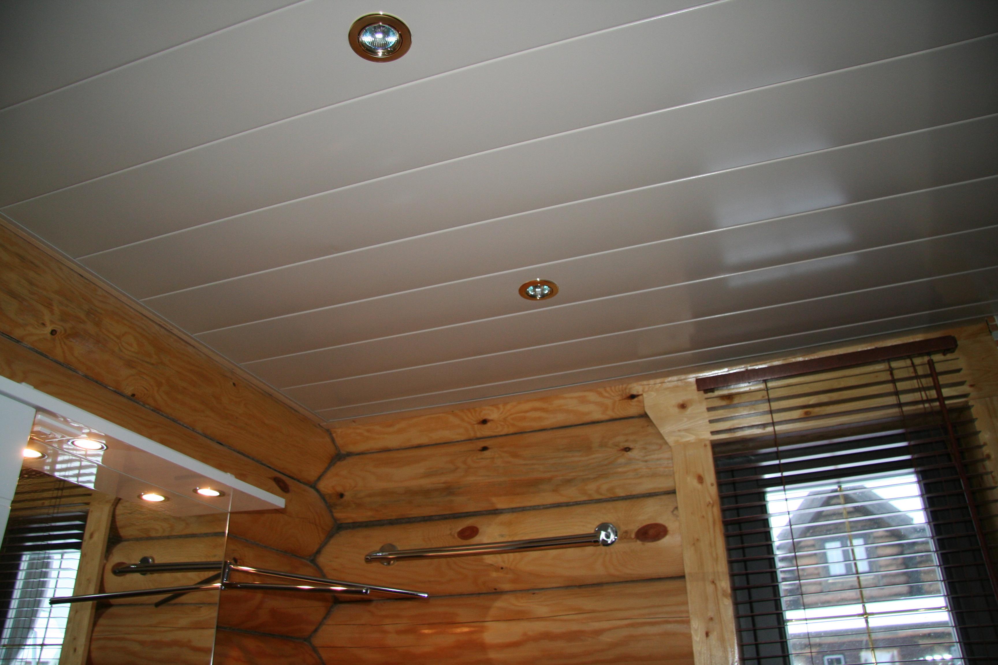 Сочетание потолка из пластиковых панелей с деревянными стенами