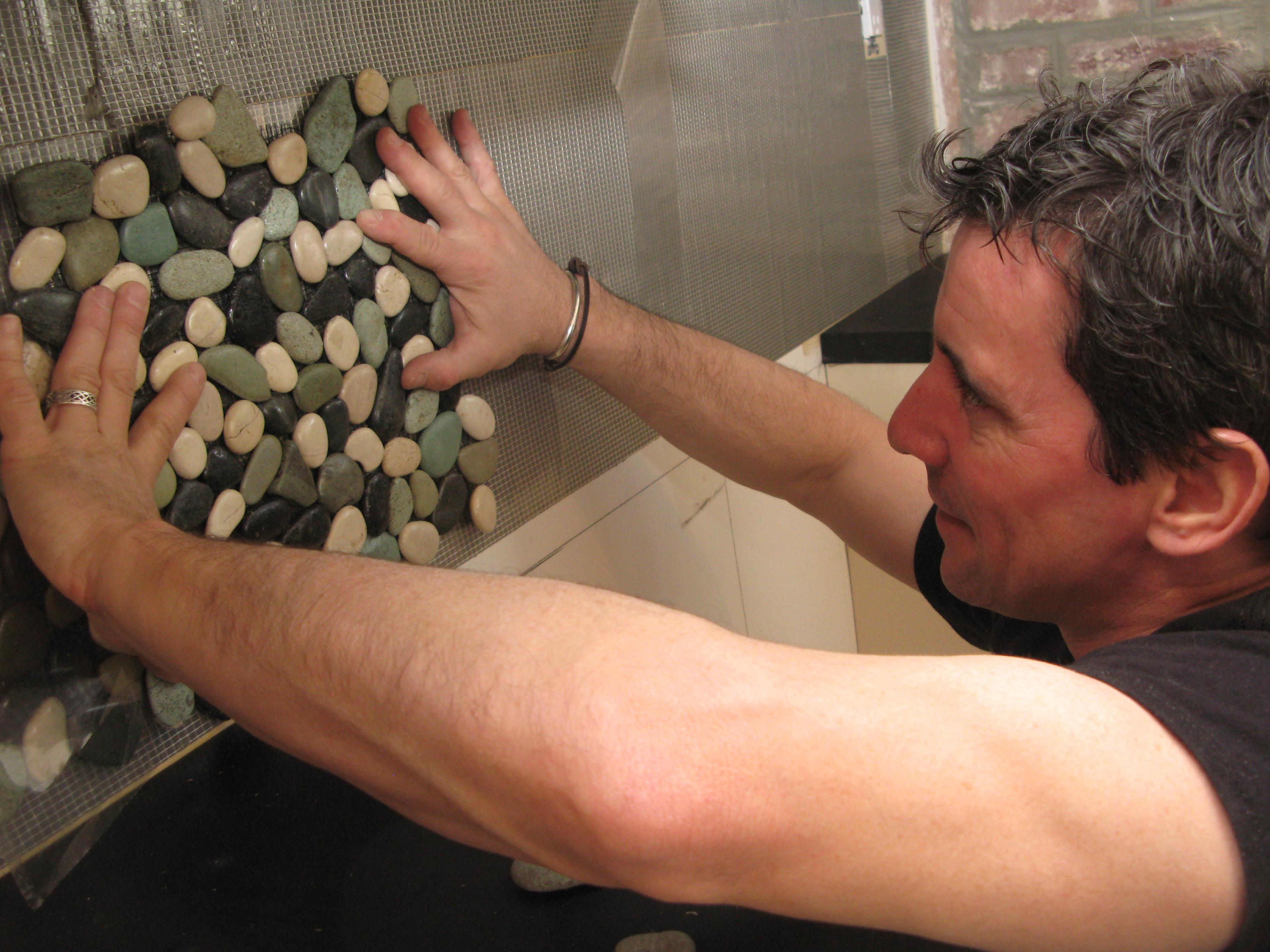 Процесс укладки мозаики на стену