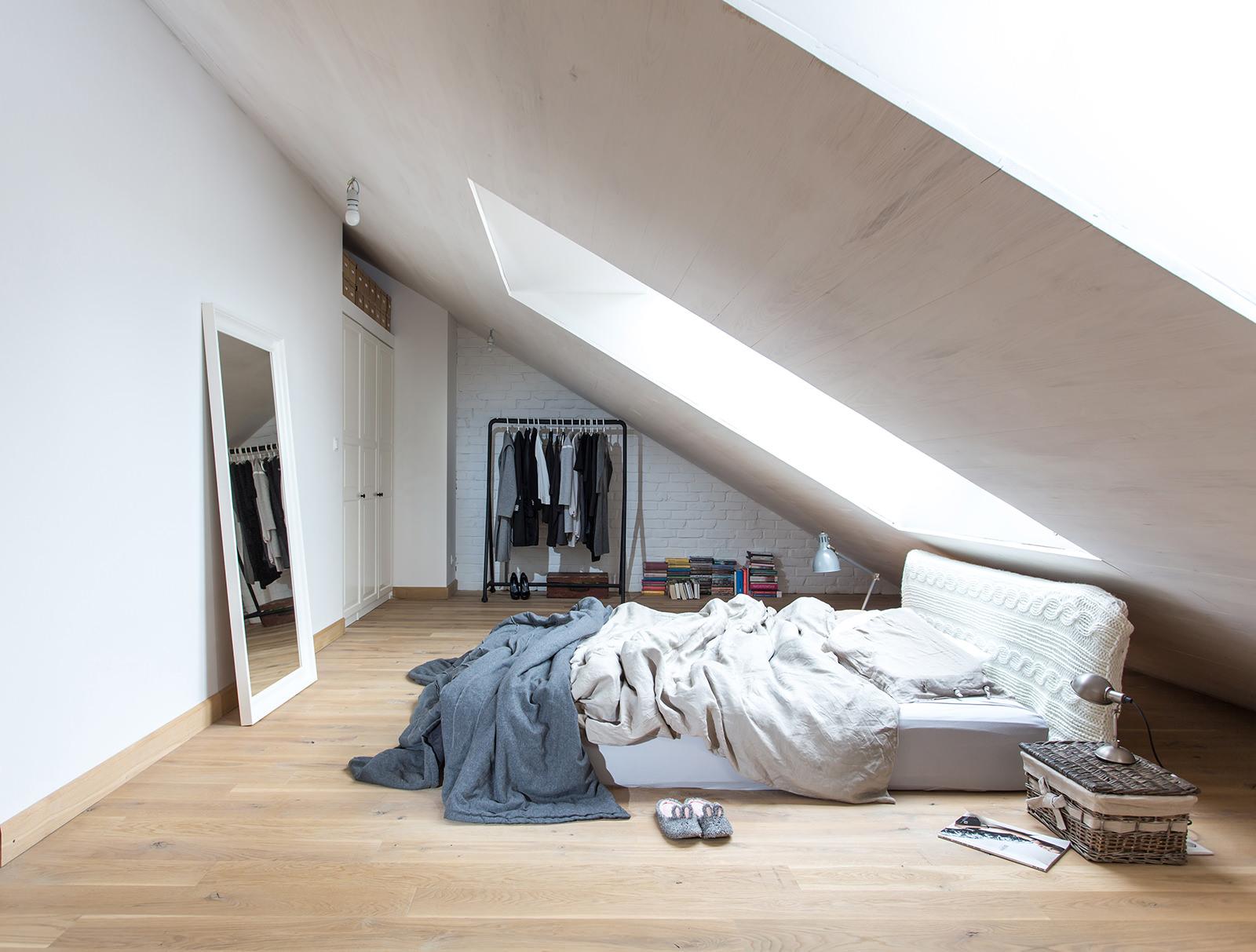 Много естественного освещения этой модерновой спальне достается за счет мансардных окон