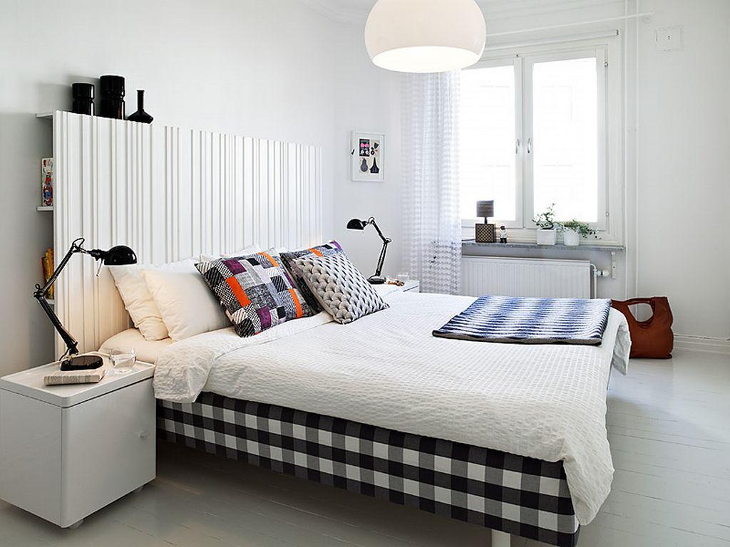 Яркий текстиль добавляет этой монохромной спальне радостный настрой